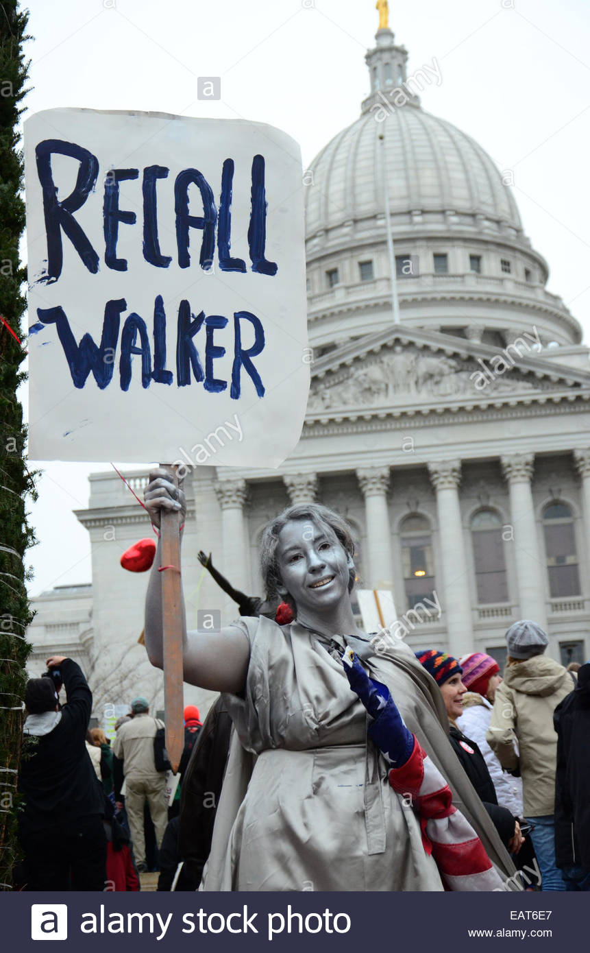 A protestor painted silver and dressed as the Statute of Liberty. - Stock Image
