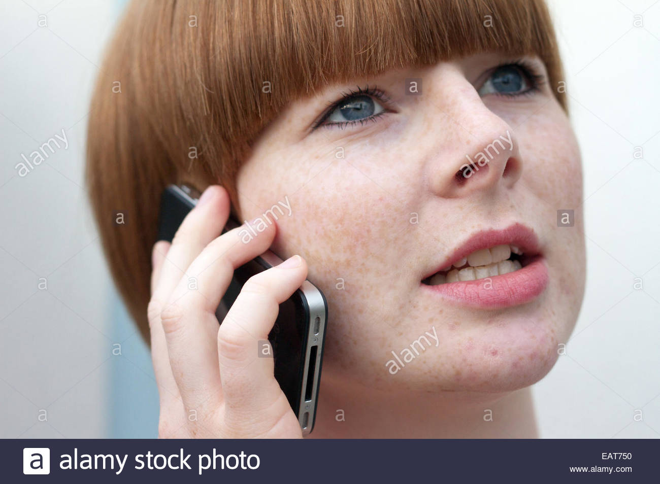 A red haired woman talks on a cellphone in Manchester, England. - Stock Image