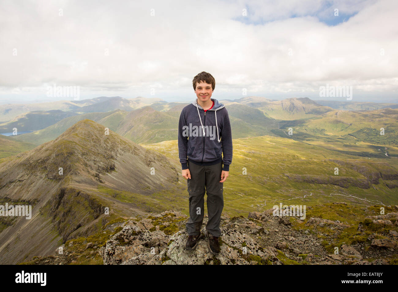 A teenage boy on the summit of Ben More, a Munro on the Isle of Mull, Scotland, UK. - Stock Image