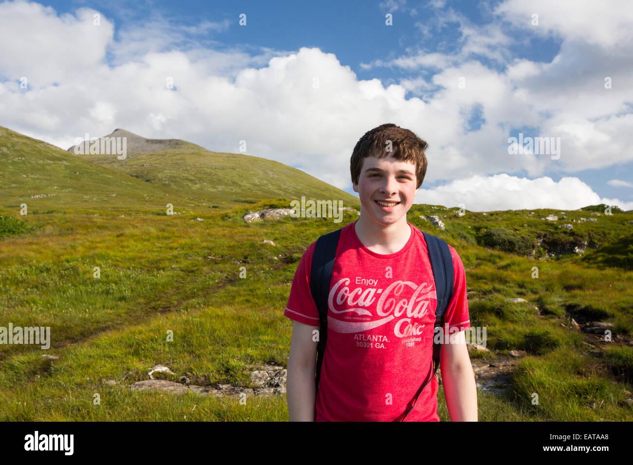 A teenage boy climbing Ben More, a Munro on the Isle of Mull, Scotland, UK. - Stock Image