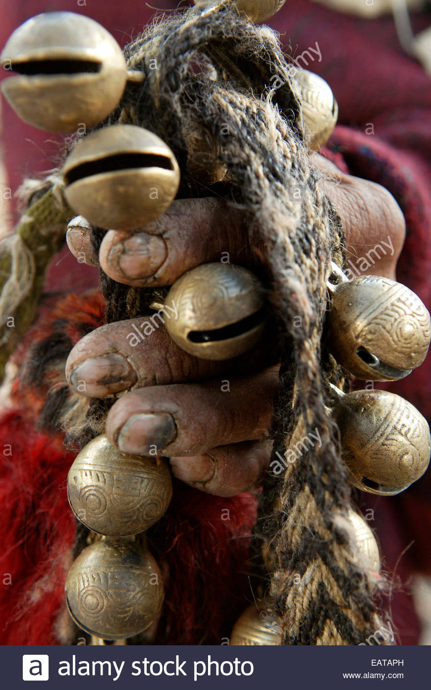 Traditional Nepalese bells held by worn hands. - Stock Image