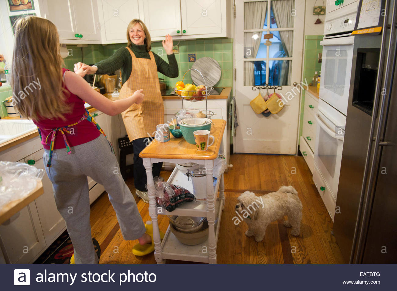 A mother and daughter dance in their kitchen