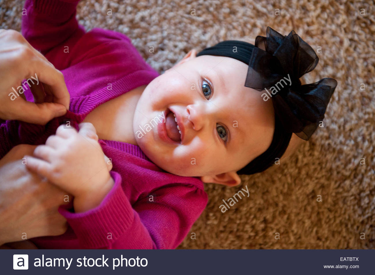 A little girl laughs while her mother tickles her at her home in Lincoln, Nebraska. - Stock Image