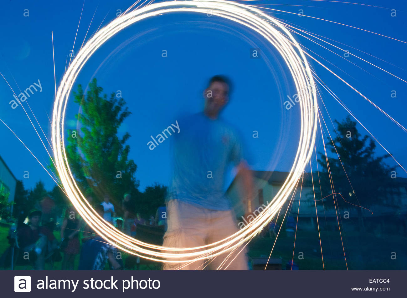 A man draws designs with a sparkler firework. - Stock Image