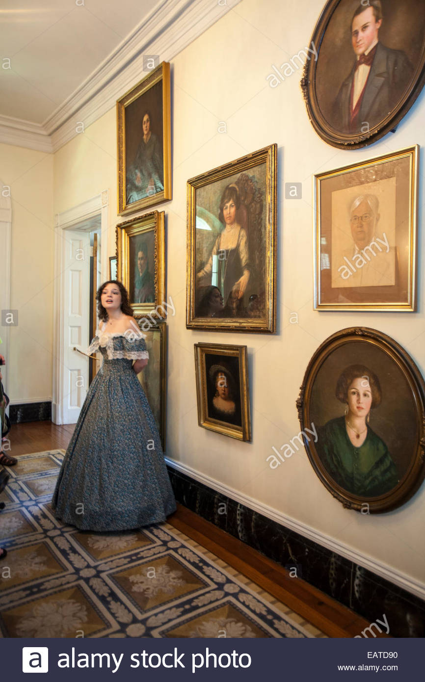 A museum docent in period clothing stands in a hallway hung with portraits of former Oak Alley Plantation owners. - Stock Image