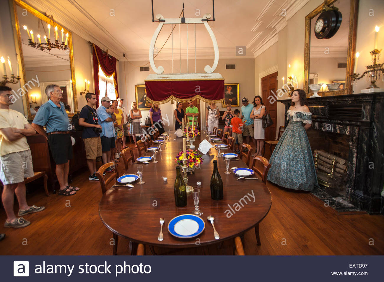 A docent talks to tourists in the dining room of the 19th century Oak Alley Plantation. - Stock Image