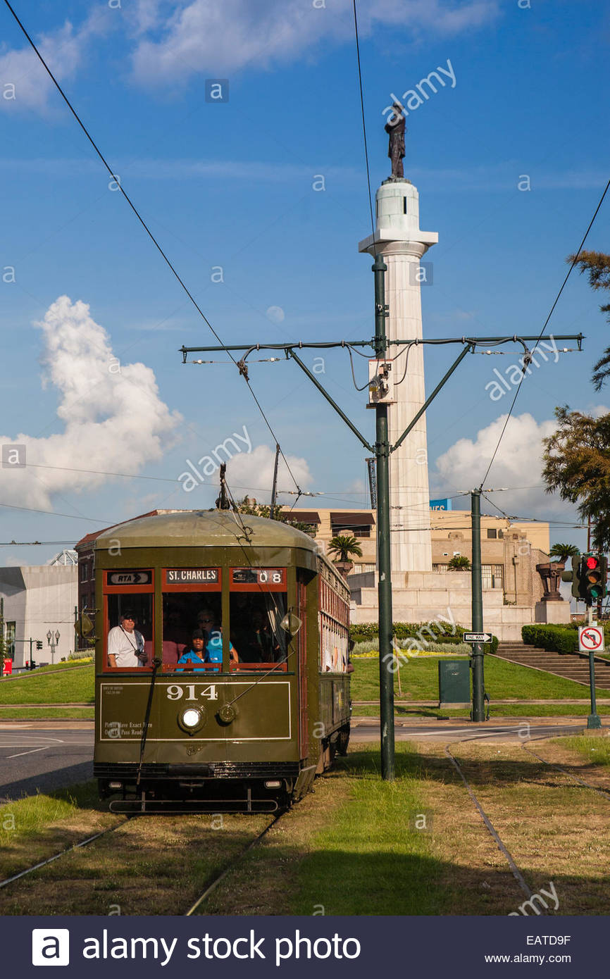 People peer through the rear window of a green streetcar in New Orleans. - Stock Image