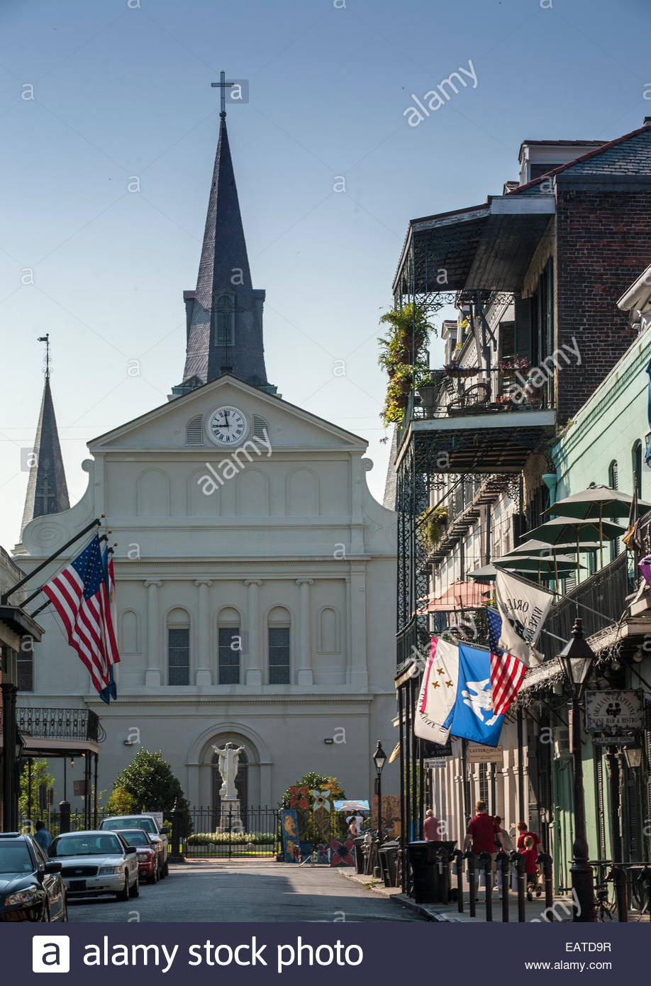 Saint Louis Cathedral and buildings ornamented with flags and balconies on Orleans Street. - Stock Image