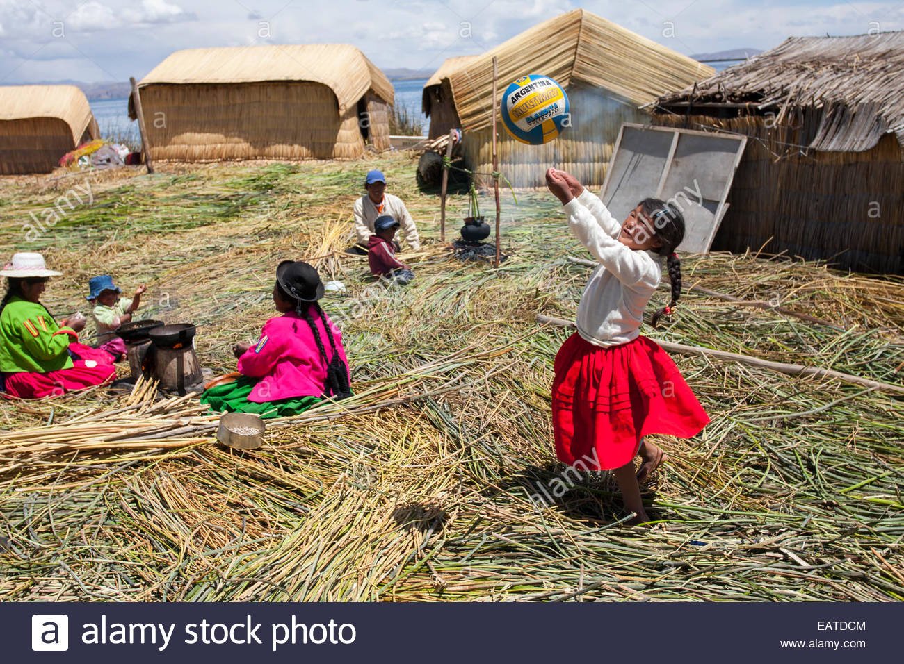 Children playing, women and men working on floating man-made reed islands. - Stock Image