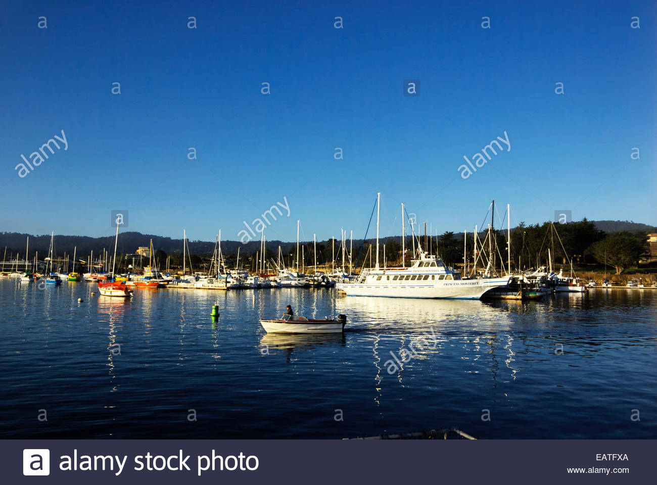 A man in a motorboat heads into Monterey Bay, Princess Monterey and other watercraft anchored in Monterey Harbor - Stock Image