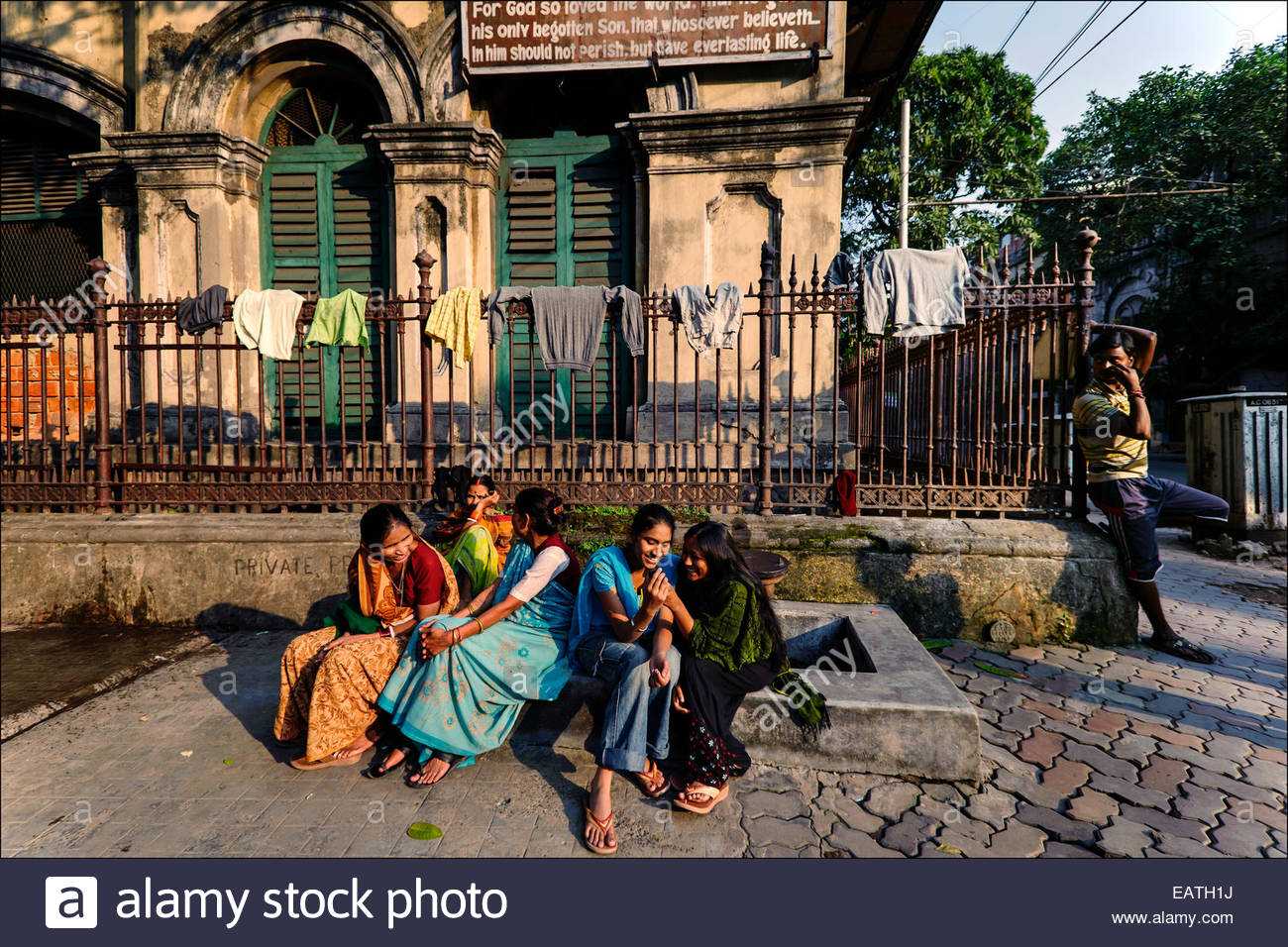 Kolkatans, some of them homeless pavement dwellers, languish on the street in front of Lee Memorial School. - Stock Image