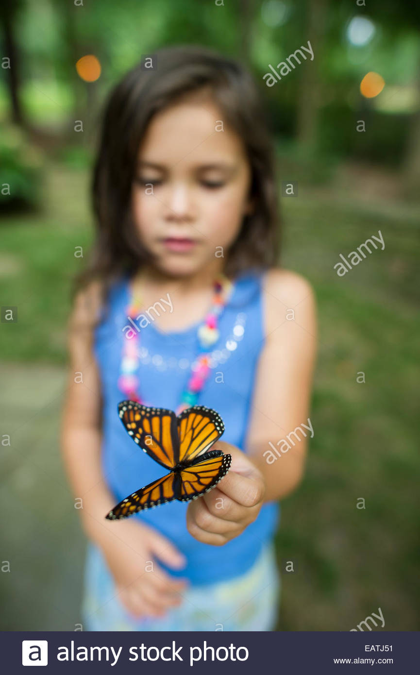 A young girl holds a preserved butterfly. - Stock Image