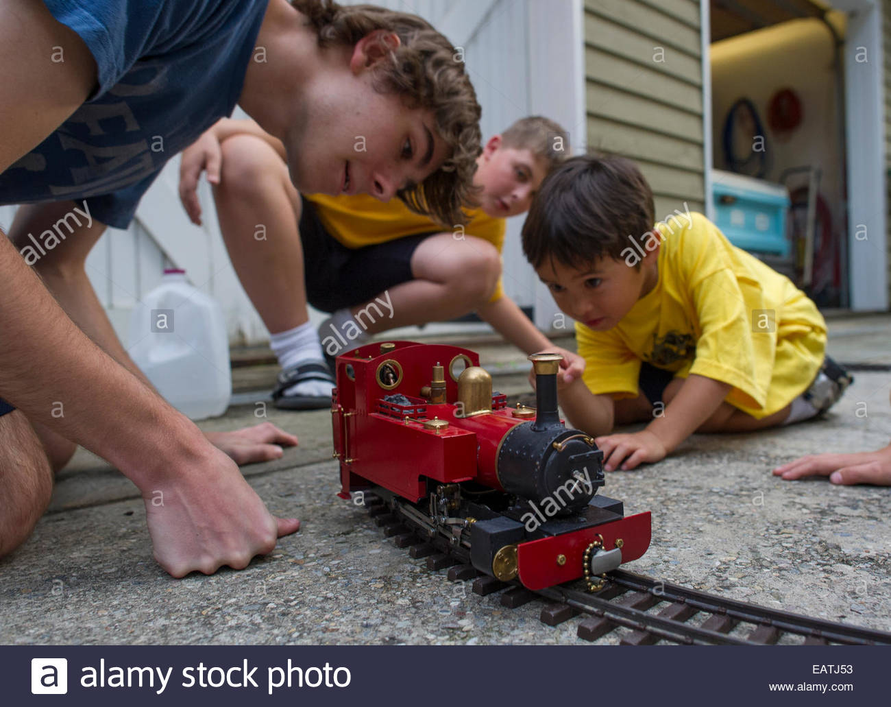 Cousins play with a G-scale toy steam train. Stock Photo