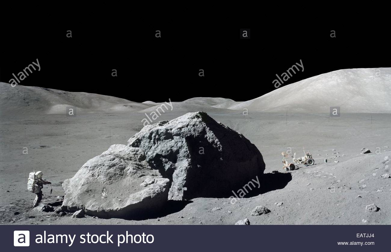Apollo 17 astronaut Harrison Schmitt examines a huge boulder during the final moonwalk of the last lunar landing - Stock Image