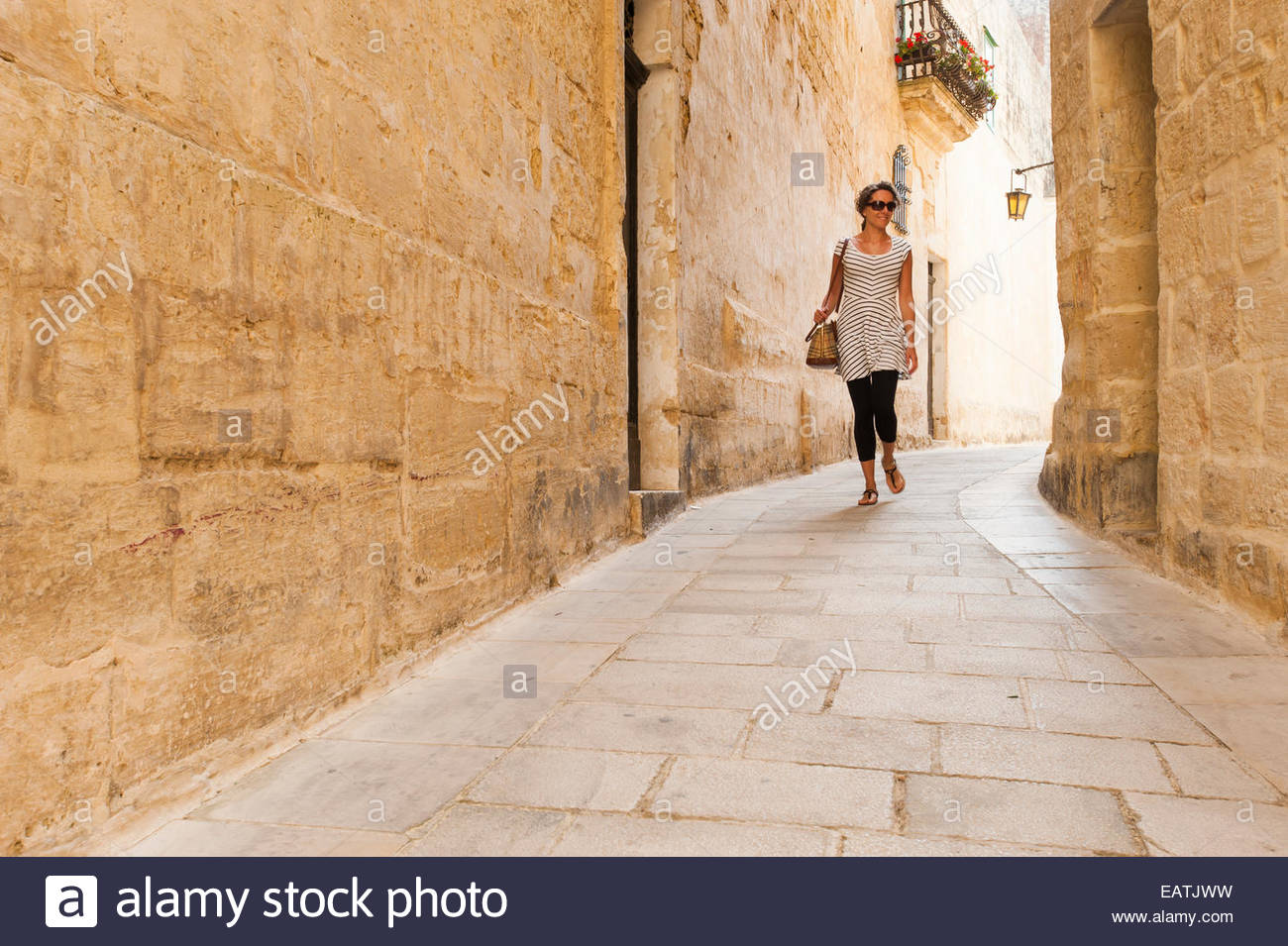 A tourist explores the backstreets of the old town of Mdina in Malta Stock Photo