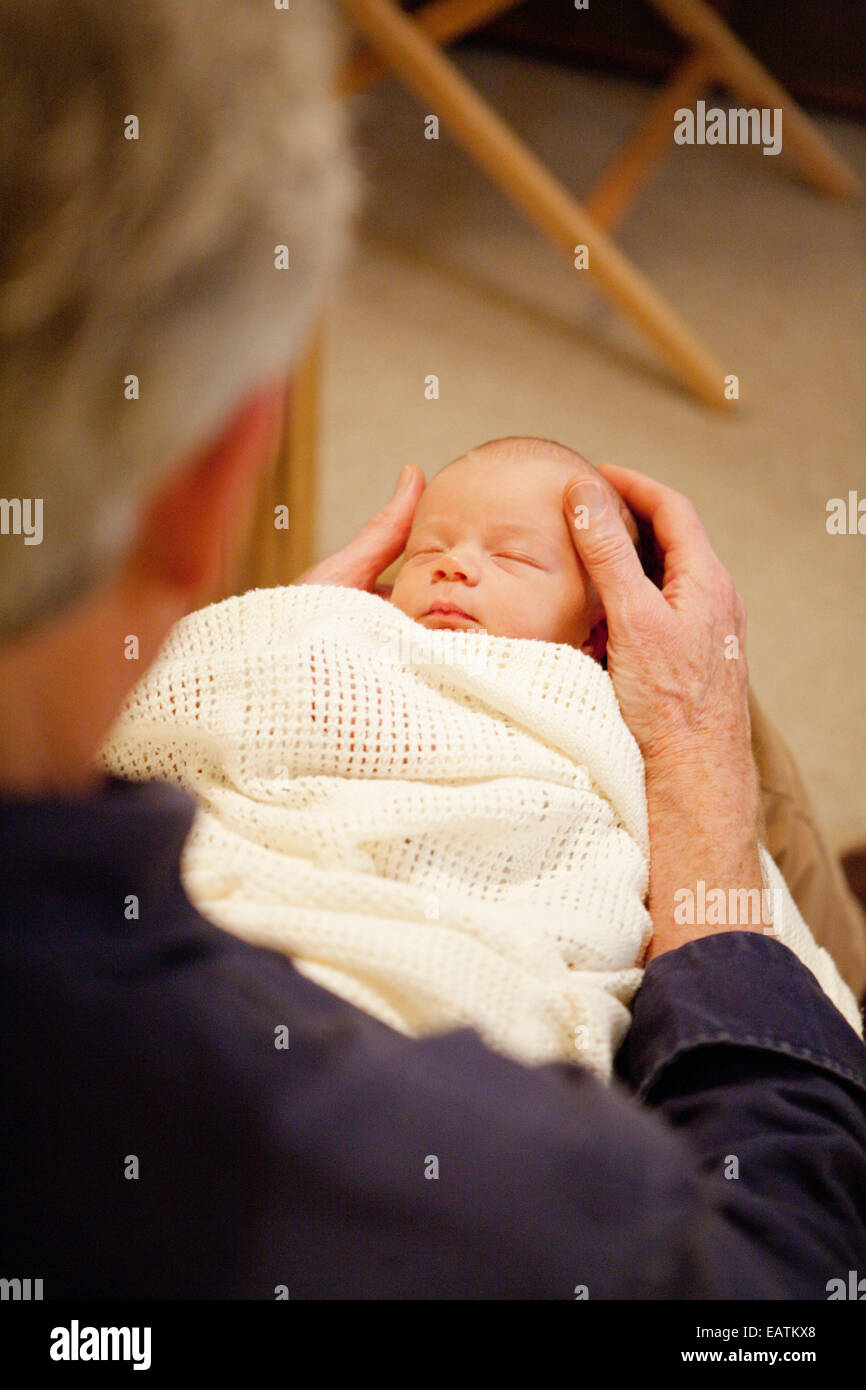 Baby wrapped up in blanket asleep in grandfather's lap - Stock Image
