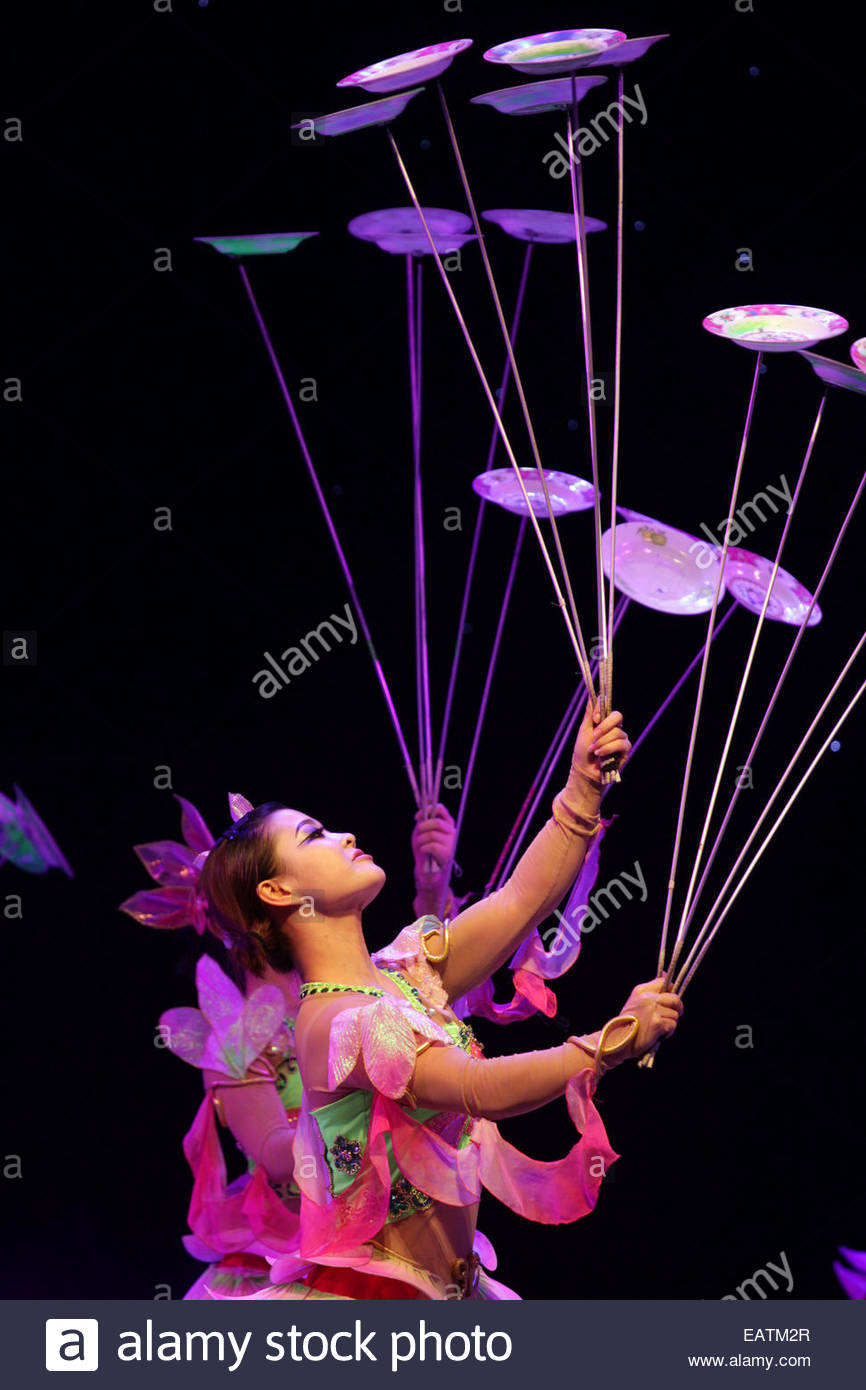 Costumed dancers balance props on stage during a performance. - Stock Image