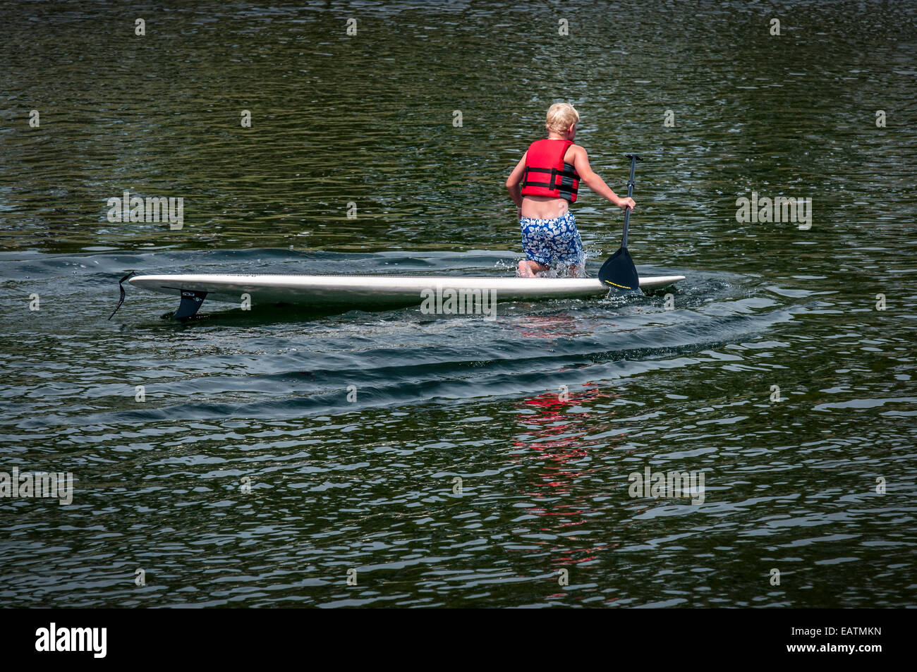 This young boy is having so much fun on his paddle board, he did not realize that his swim trunks are falling down. - Stock Image