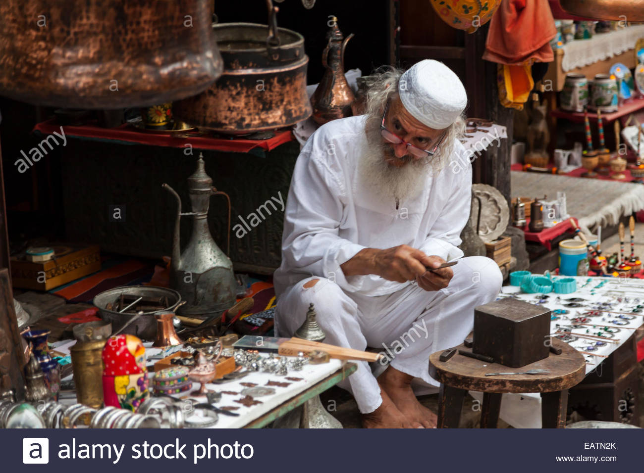Portrait of an Muslim shopkeeper and metal worker with his wares. - Stock Image