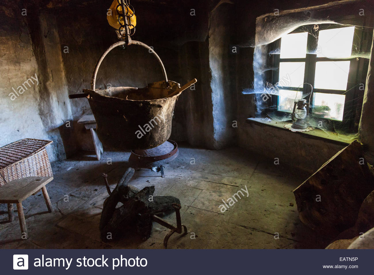 A large kettle hanging over an unlit fire in a traditional kitchen. - Stock Image