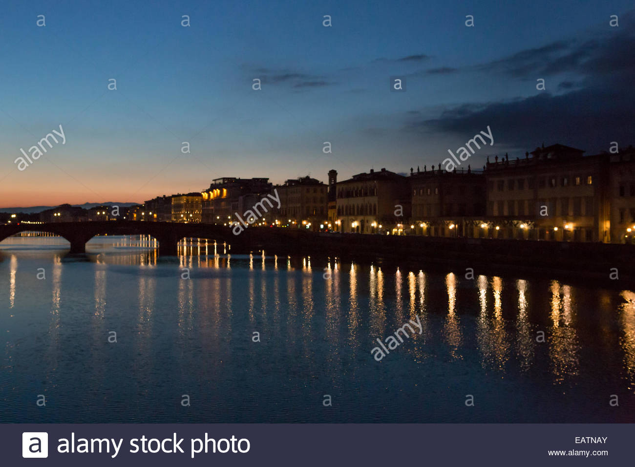 The city of Florence is divided by the Arno River as seen at sunset. - Stock Image