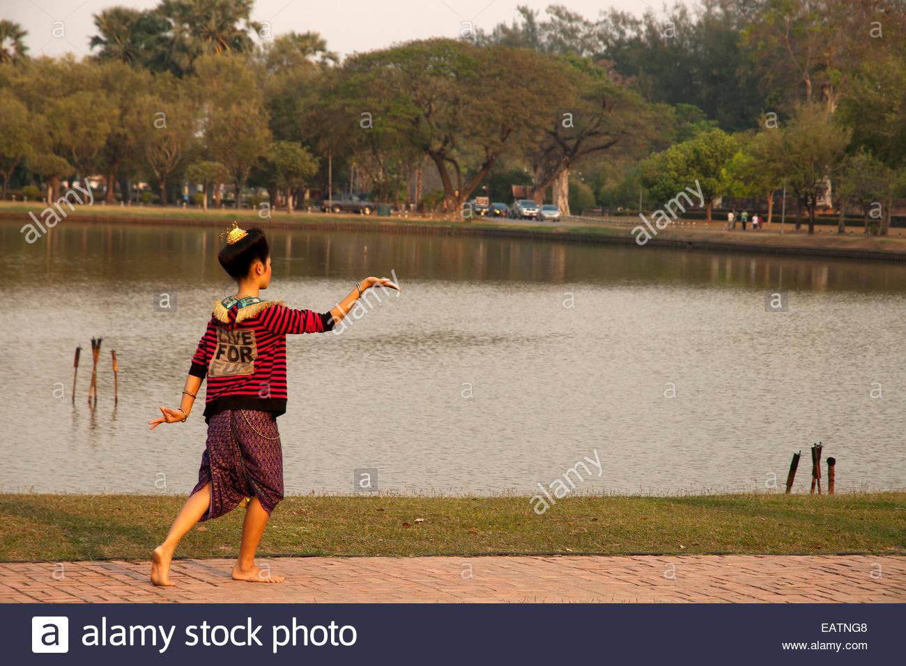 A woman dances outside of Wat Sa Sri Temple. - Stock Image