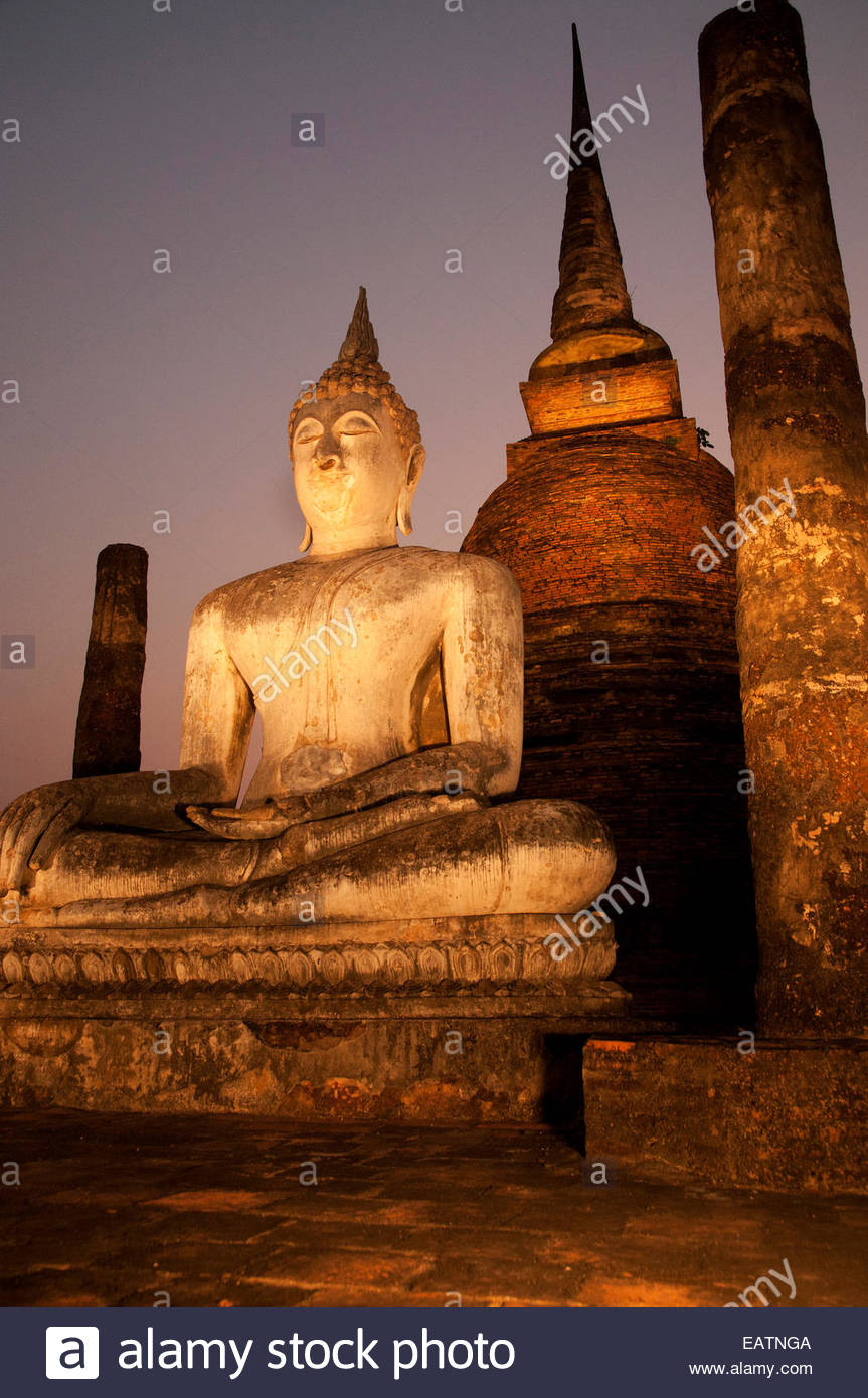 A Buddha statue sits in front of a stupa at Wat Sa Sri Temple. - Stock Image