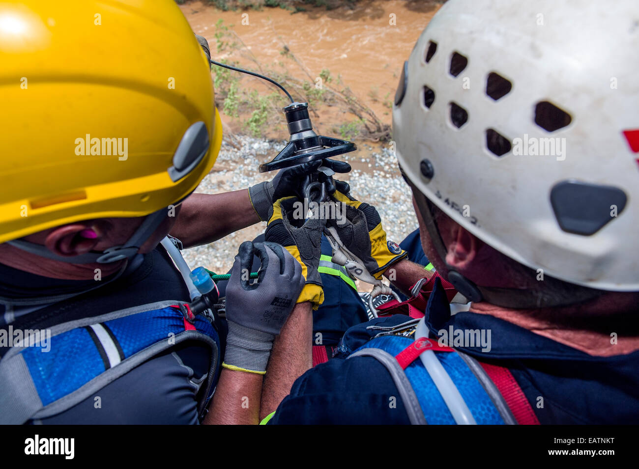 Airforce and police rescue team descend on a winch to a flooded river. - Stock Image