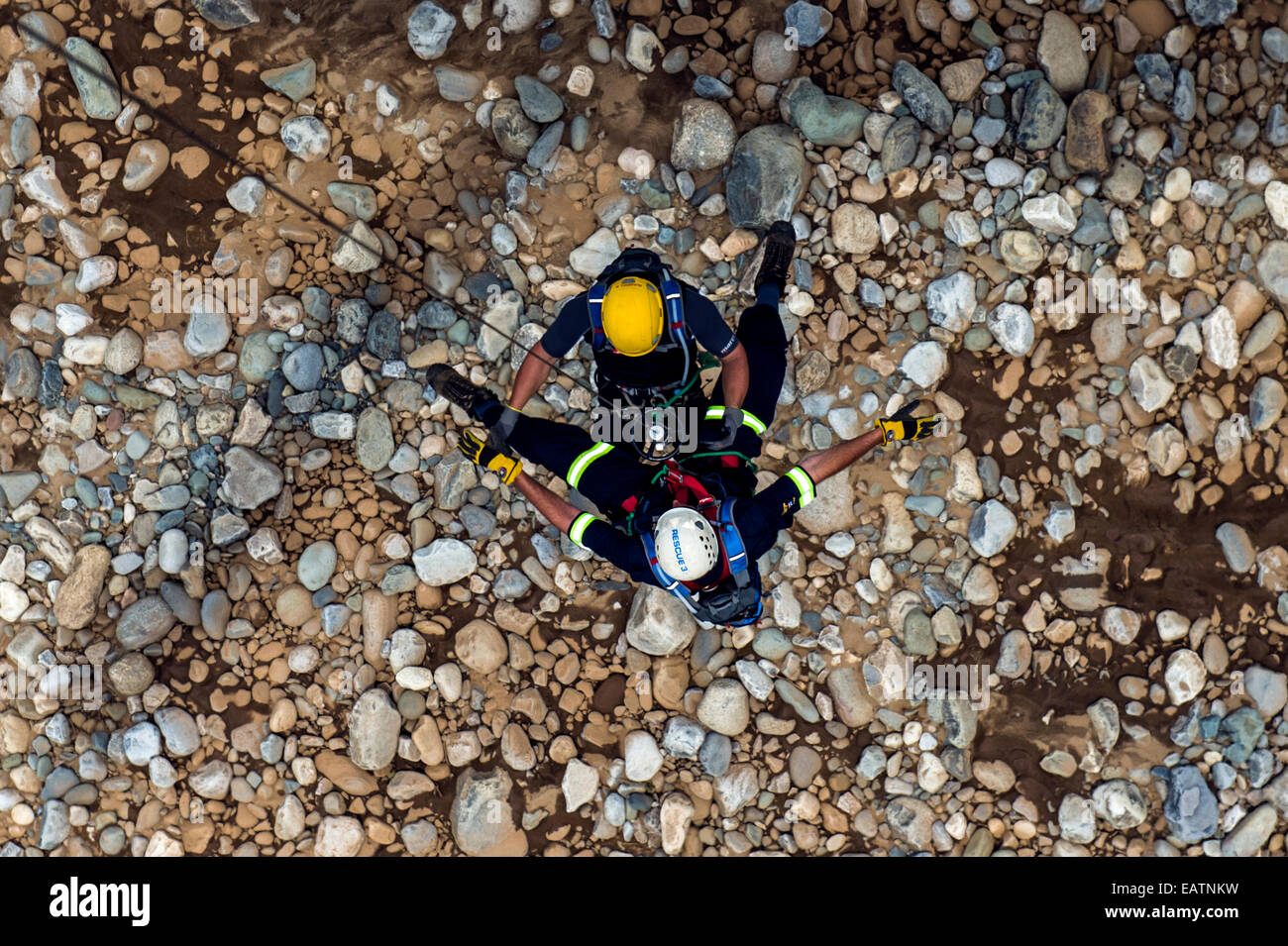 Airforce and police rescue team descends on a winch to a rocky slope. - Stock Image