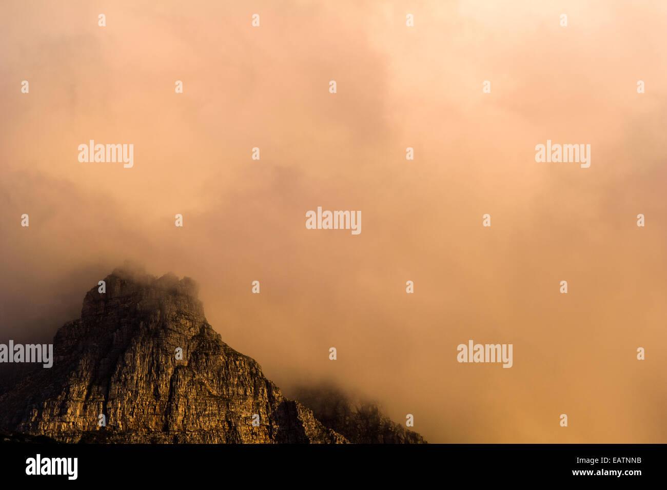 Menacing sunset storm clouds consume a rugged coastal mountain range. - Stock Image