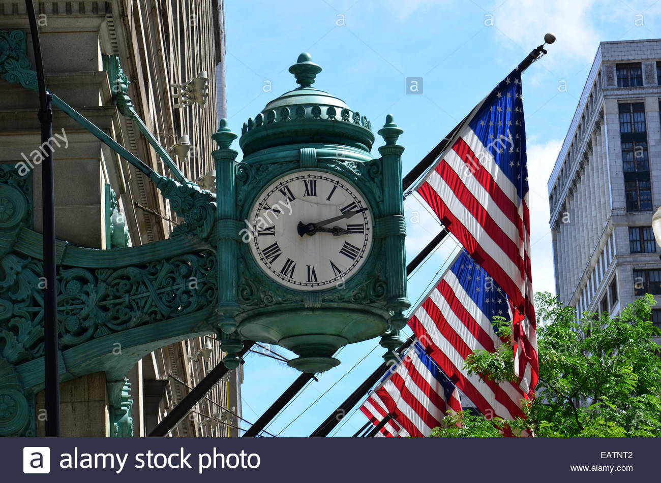 A clock with a white face and Roman numerals on the Macy's building. - Stock Image