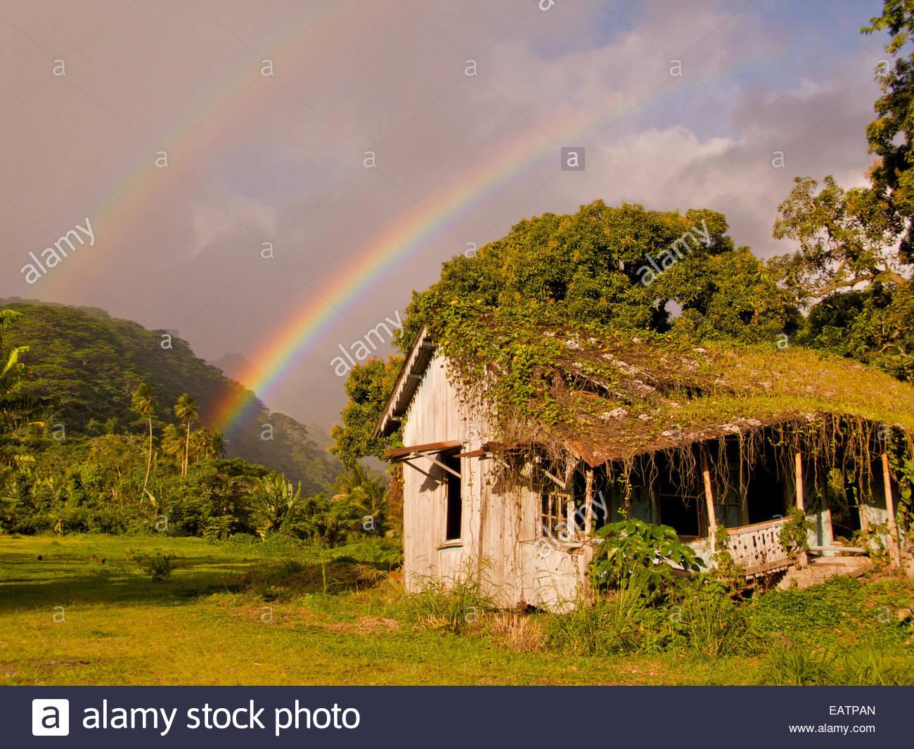 A double rainbow appears over an abandoned house in rural Tahiti. - Stock Image
