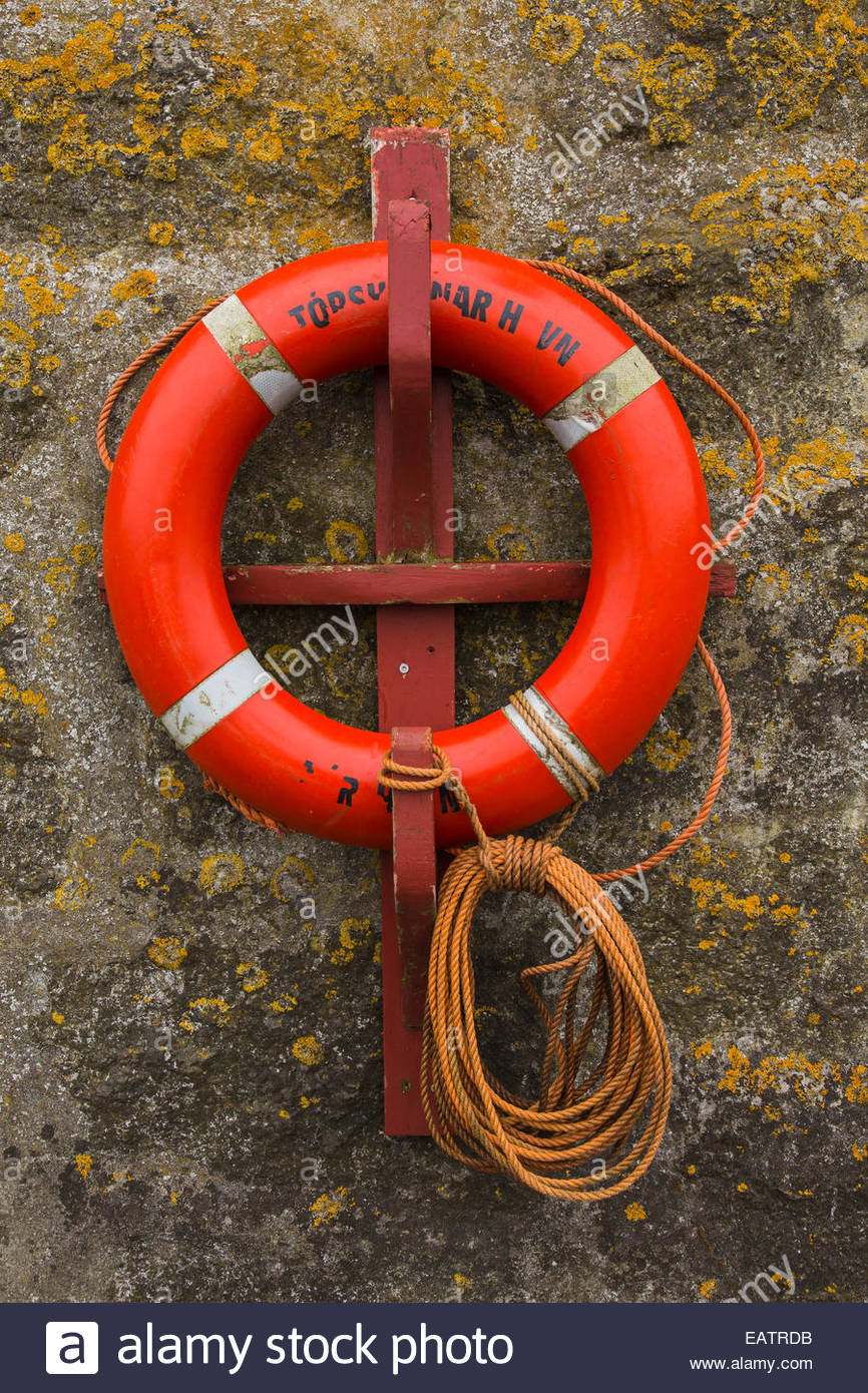 Close up of an orange nautical life ring on a stone wall. - Stock Image