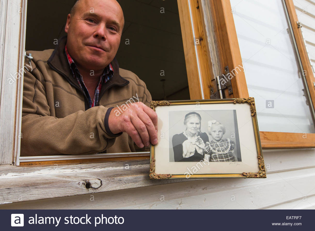 A man in a window holds an old black and white photograph. - Stock Image