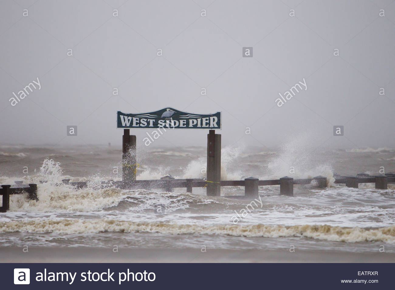 Hurricane Isaac's storm surge waves crashing into the West Side Pier. - Stock Image