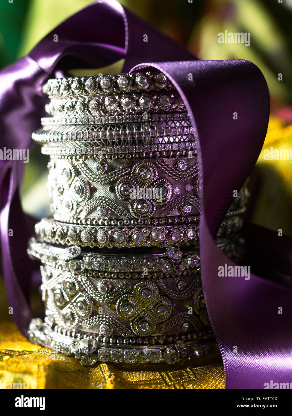 silver ornate bangle bracelets stacked with a decorative purple ribbon on a yellow green background - Stock Image