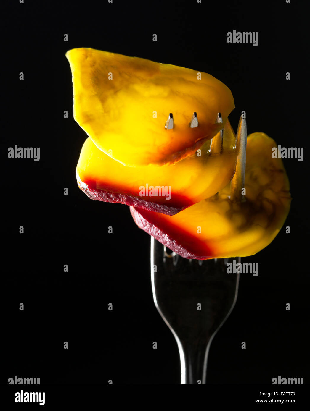 Yellow beets on a silver fork against black background - Stock Image