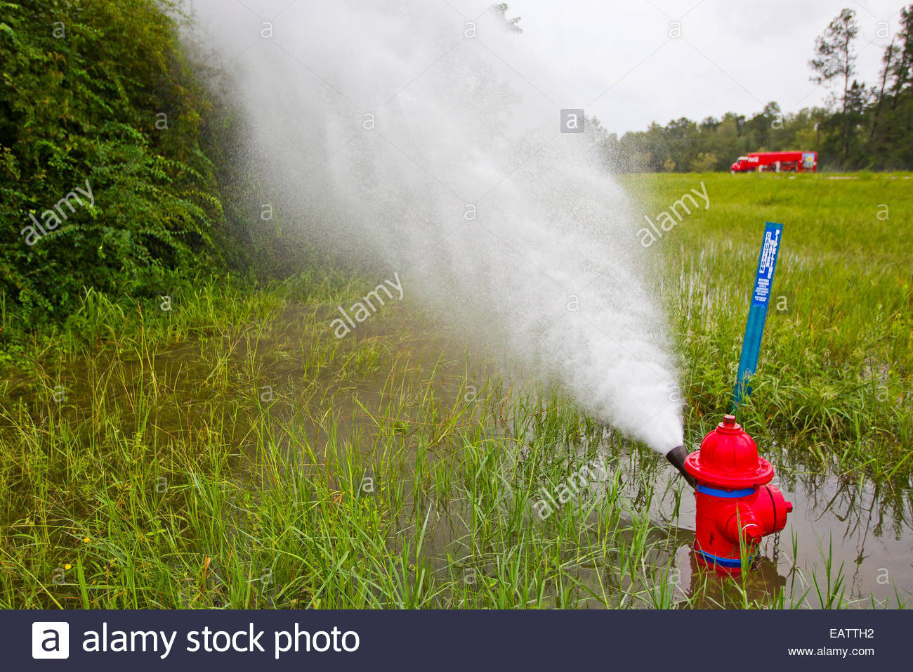 A fire hydrant releases water pressure from heavy rains due to Hurricane Isaac. Stock Photo