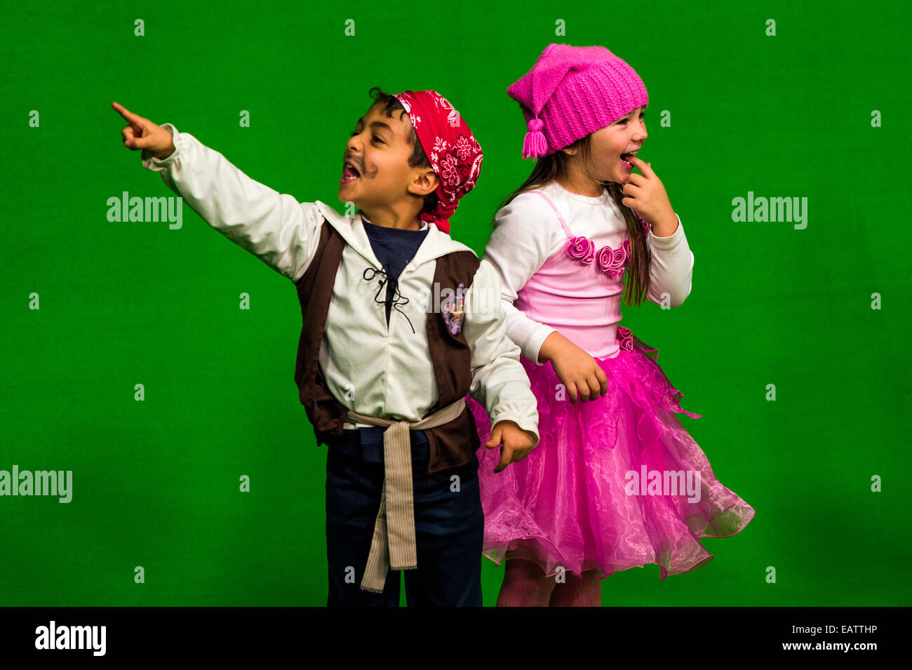 School children performing in front of a green screen at a studio. - Stock Image