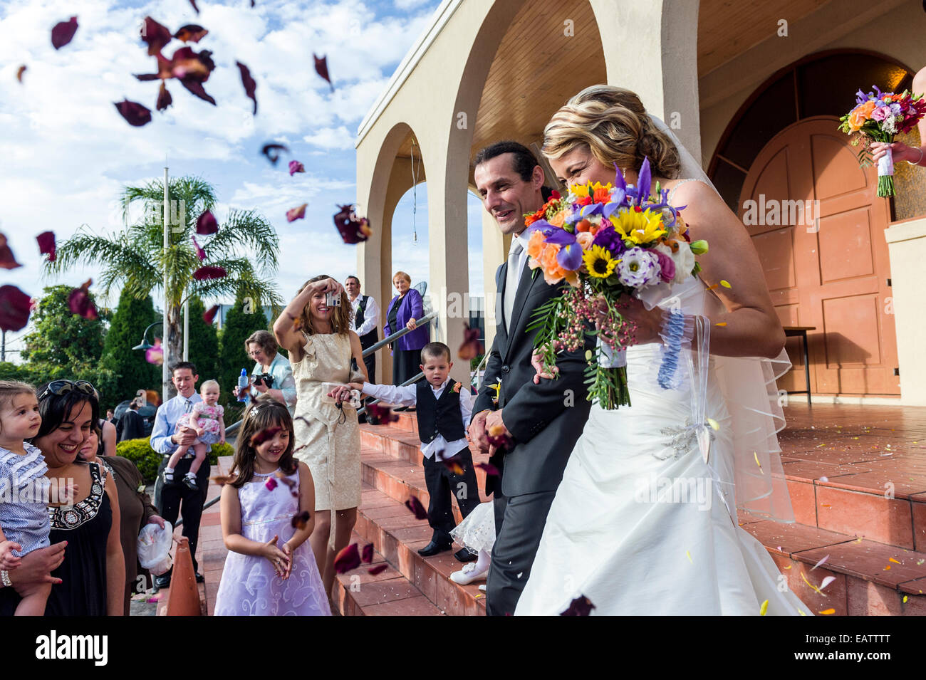 Confetti and rose petal shower a bride and groom at a Greek