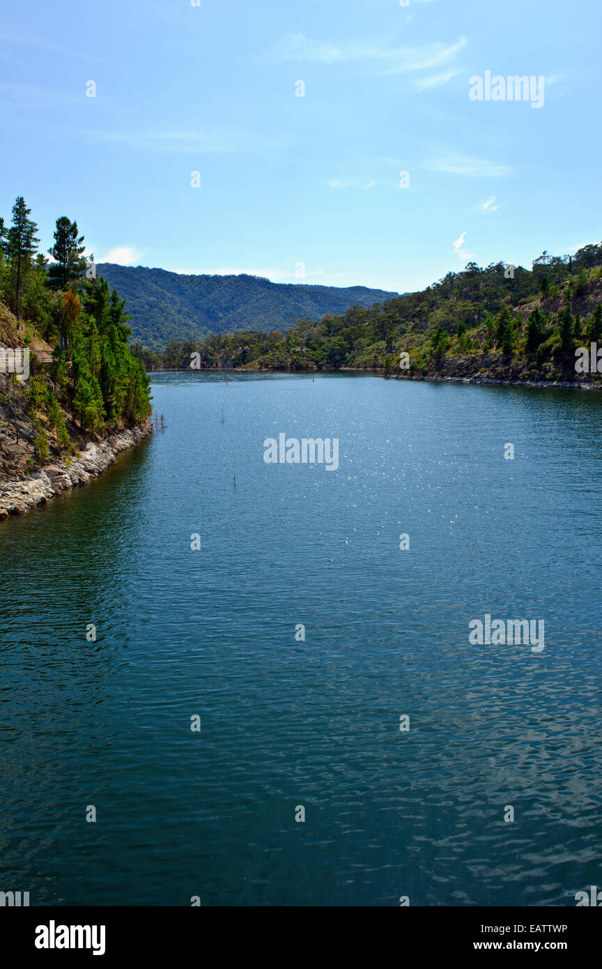 A manmade dam filled to capacity with water to supply a nearby city. - Stock Image