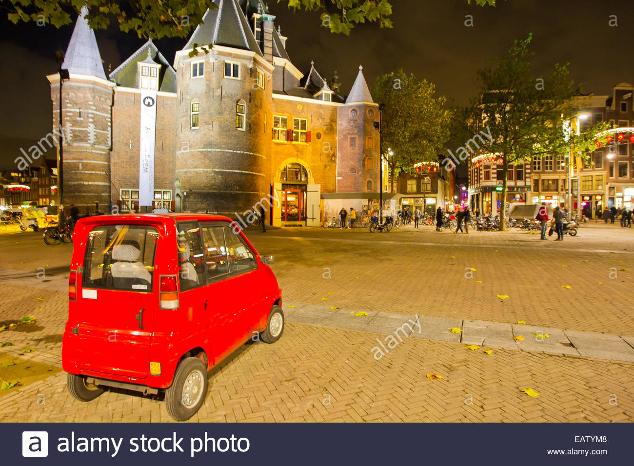 A little red Smart Car parked in front of a castle. - Stock Image
