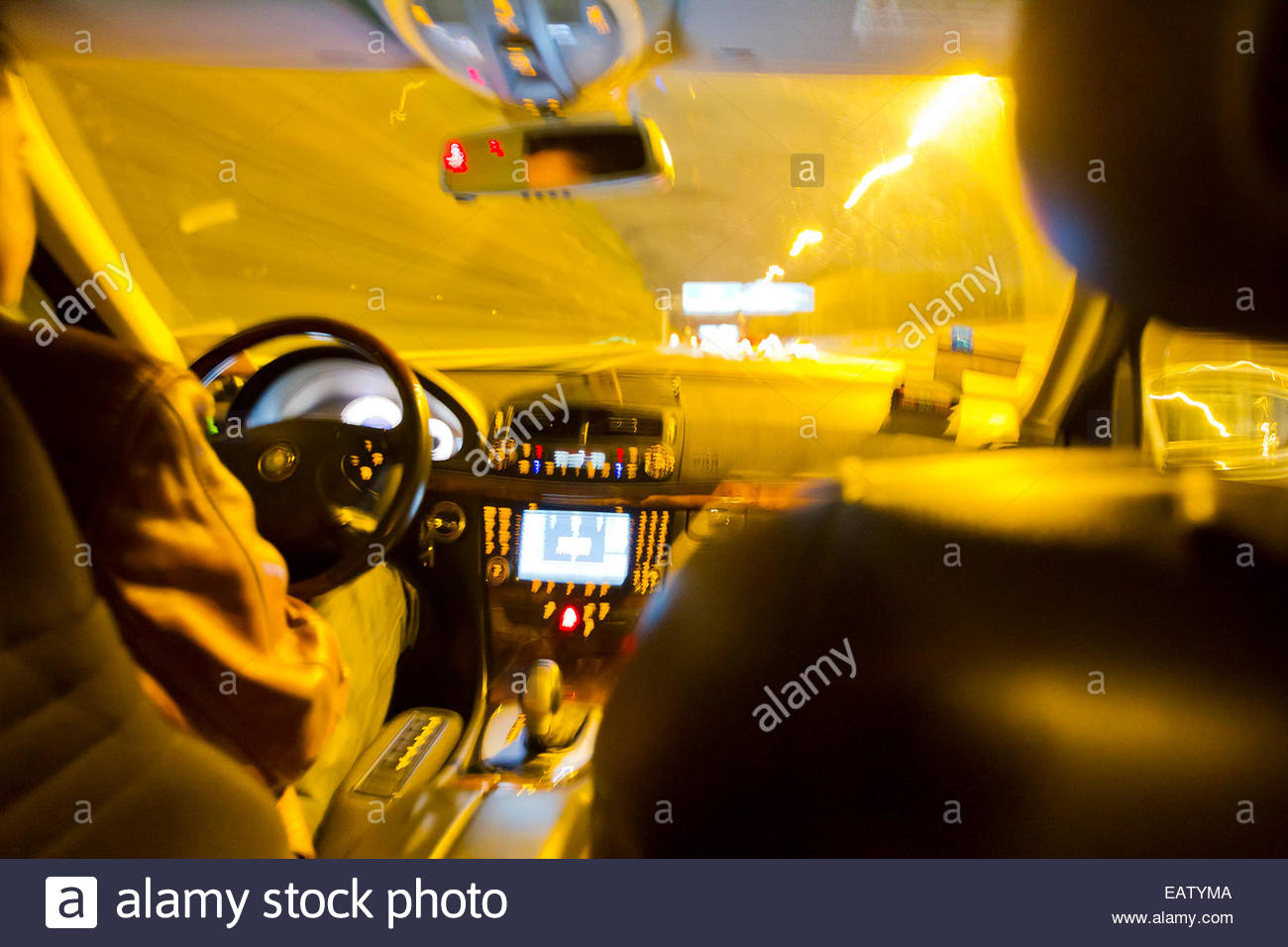 Long exposure from the backseat of a taxi cab driving at night. - Stock Image