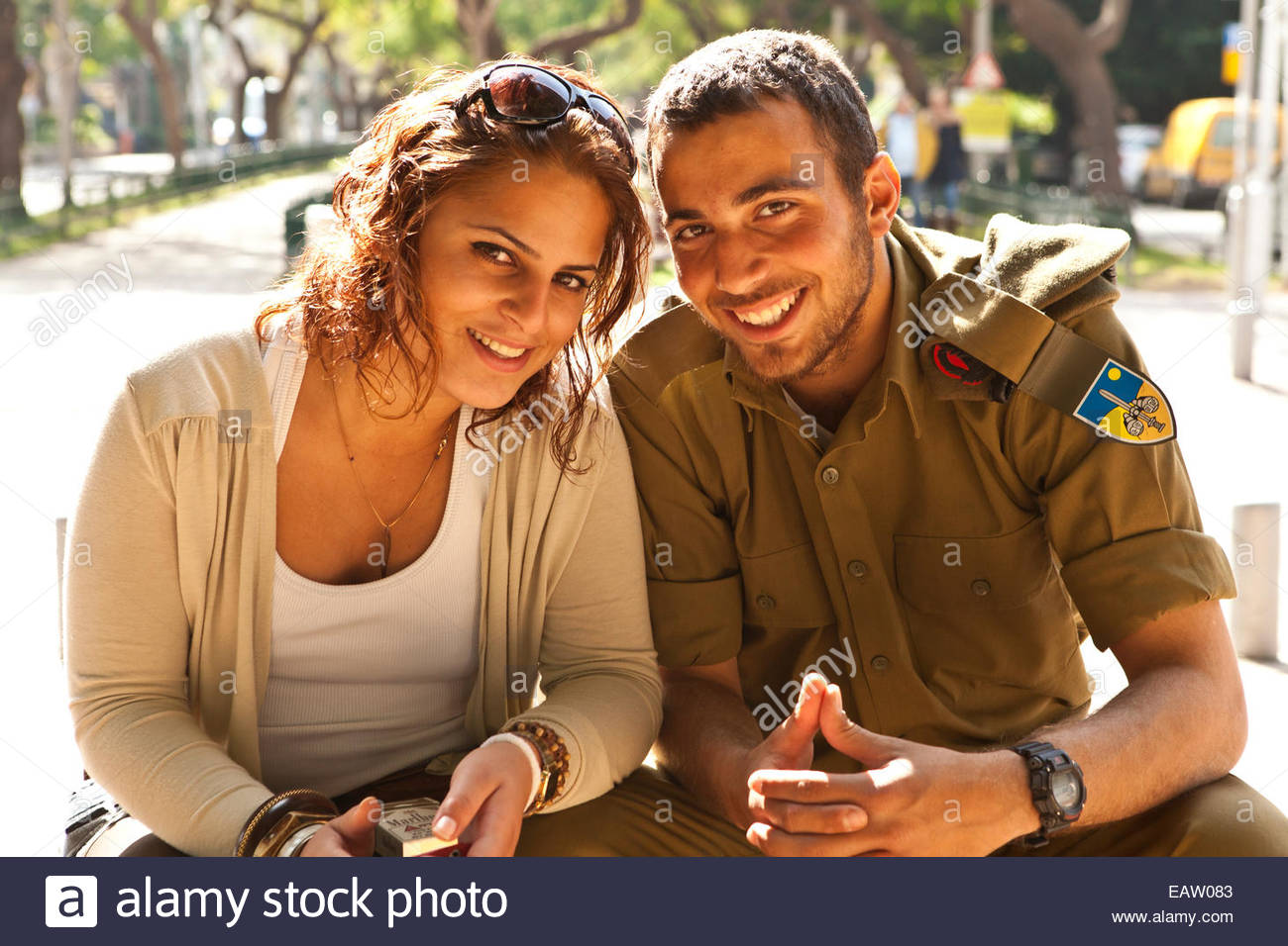 An attractive young couple poses on Rothschild Boulevard. - Stock Image
