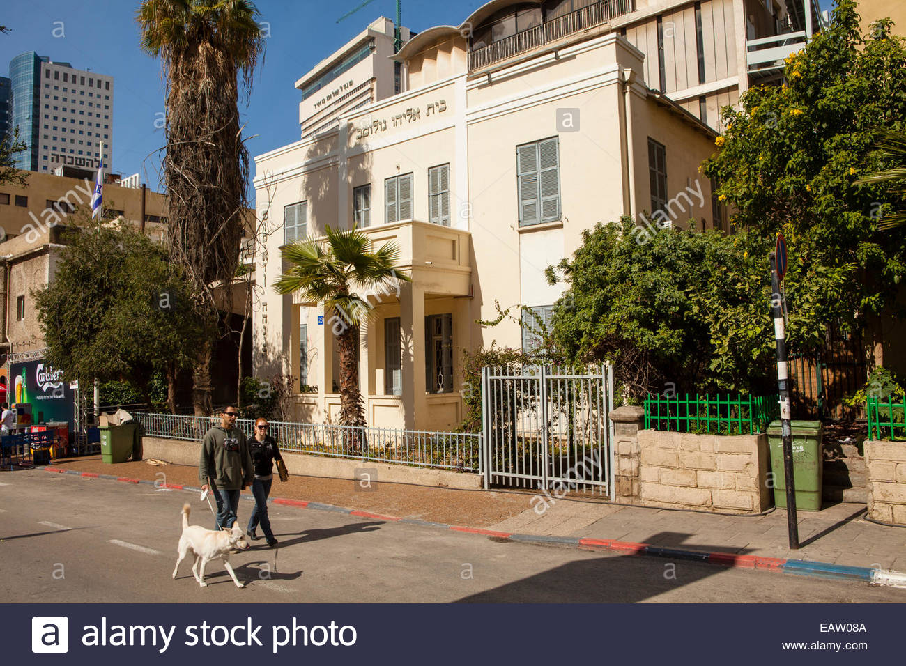 A couple and dog walk past Bauhaus Architecture in Tel Aviv. - Stock Image