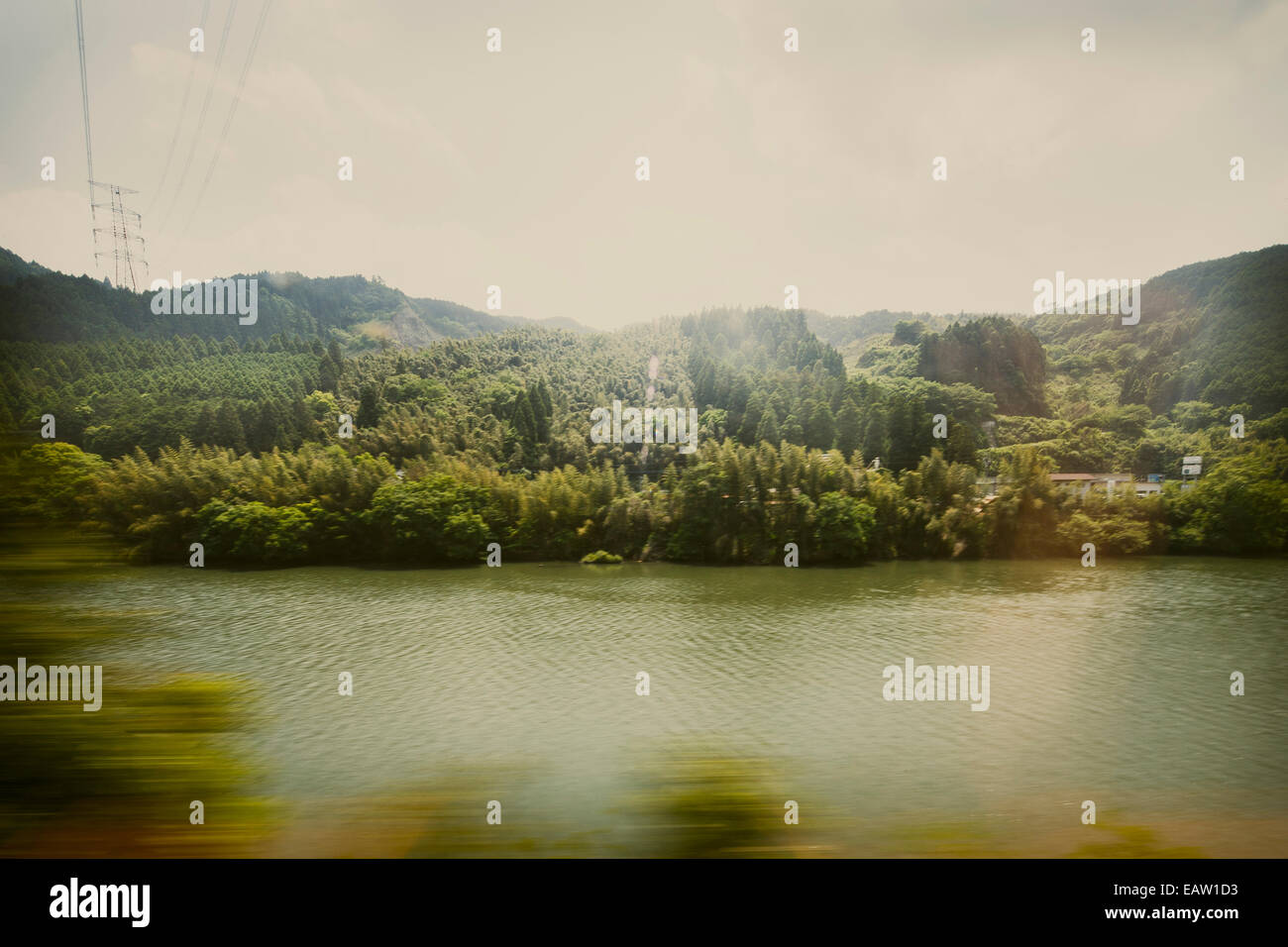 Blurry view of trees on the foreground a placid lake and lush green hilly view of urban Japan from bullet train. - Stock Image