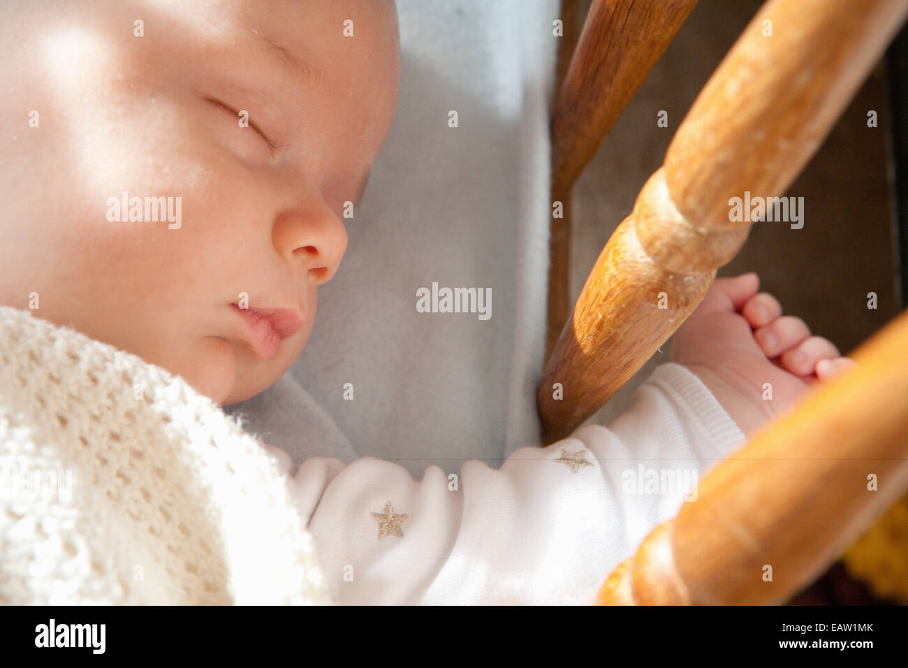 Baby asleep in crib - Stock Image