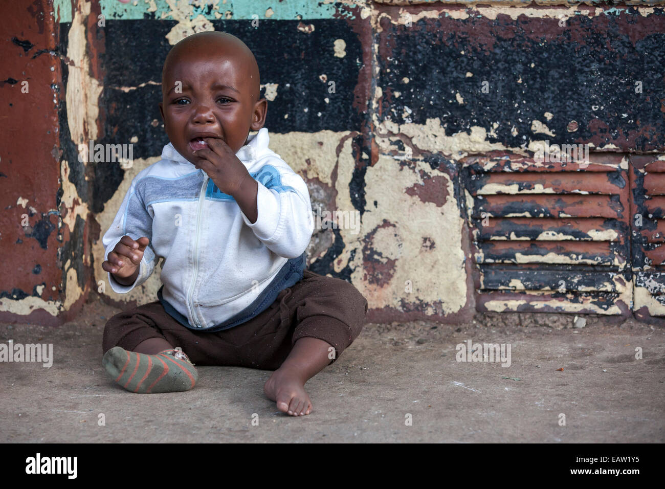 A baby cries outside one of Durban Deep Goldmine's hostels on the outskirts of Johannesburg South Africa. - Stock Image