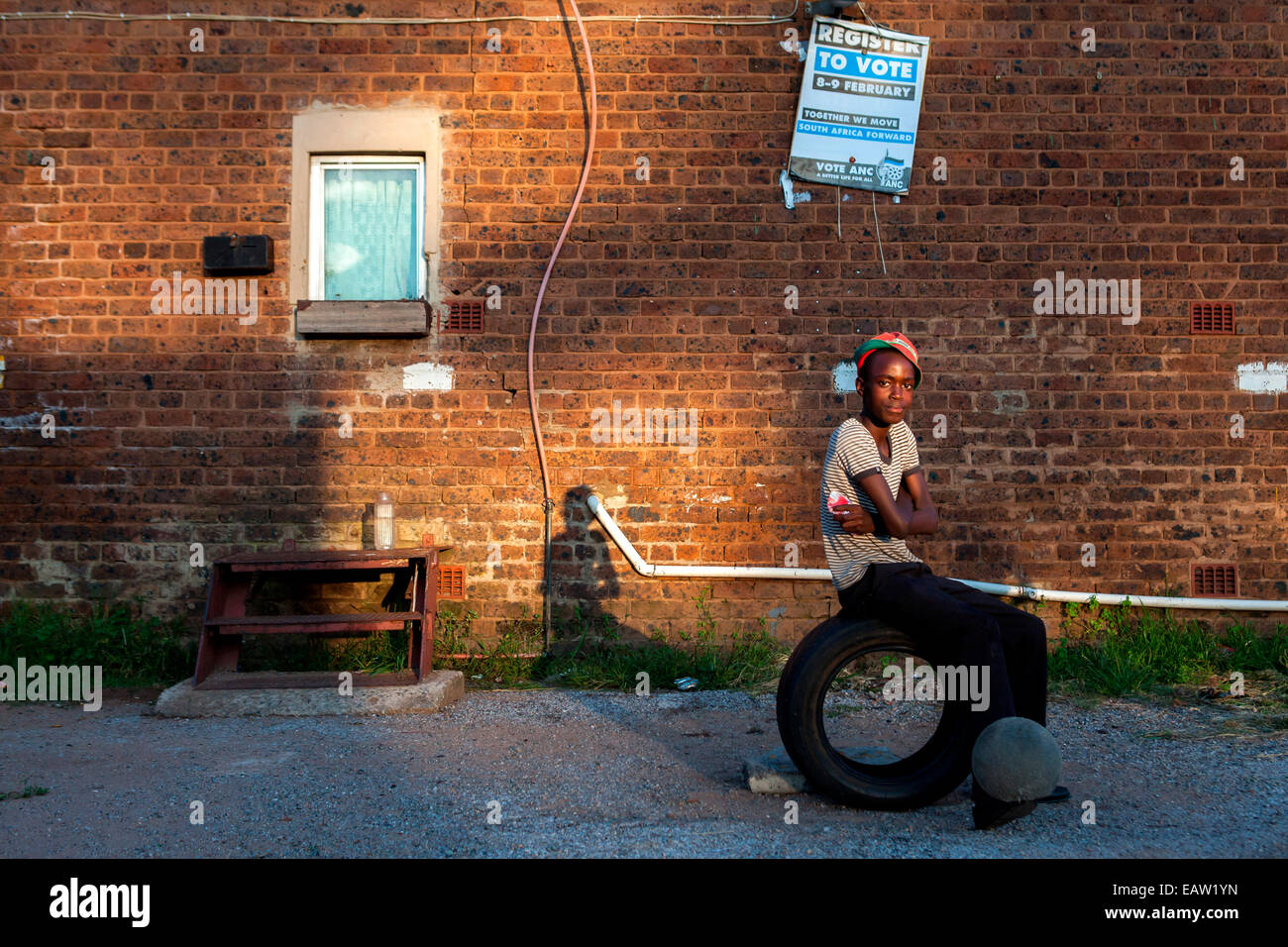 A teenaged boy sits on a tire and bounces a soccer ball on his feet at one of Durban Deep's old hostels on the - Stock Image