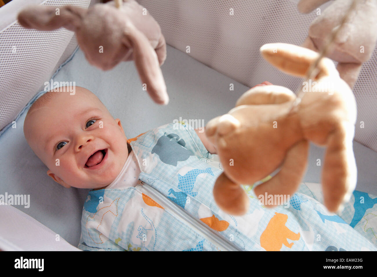 Baby in cot laughing - Stock Image